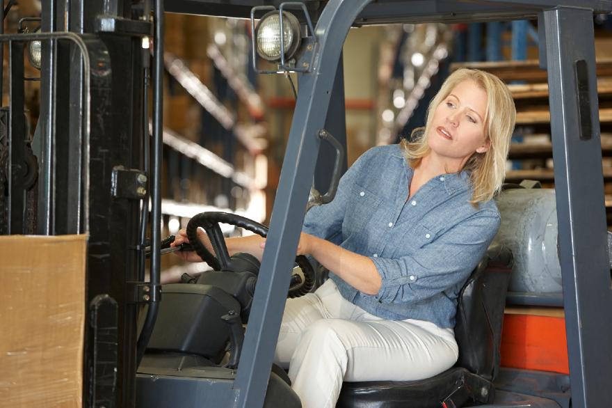 woman-driving-fork-lift-truck-in-warehouse-PFNLDSJ