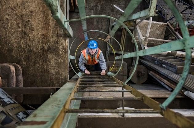 factory-worker-climbing-up-a-ladder-in-a-sheet-met-FCJ8Z52-1